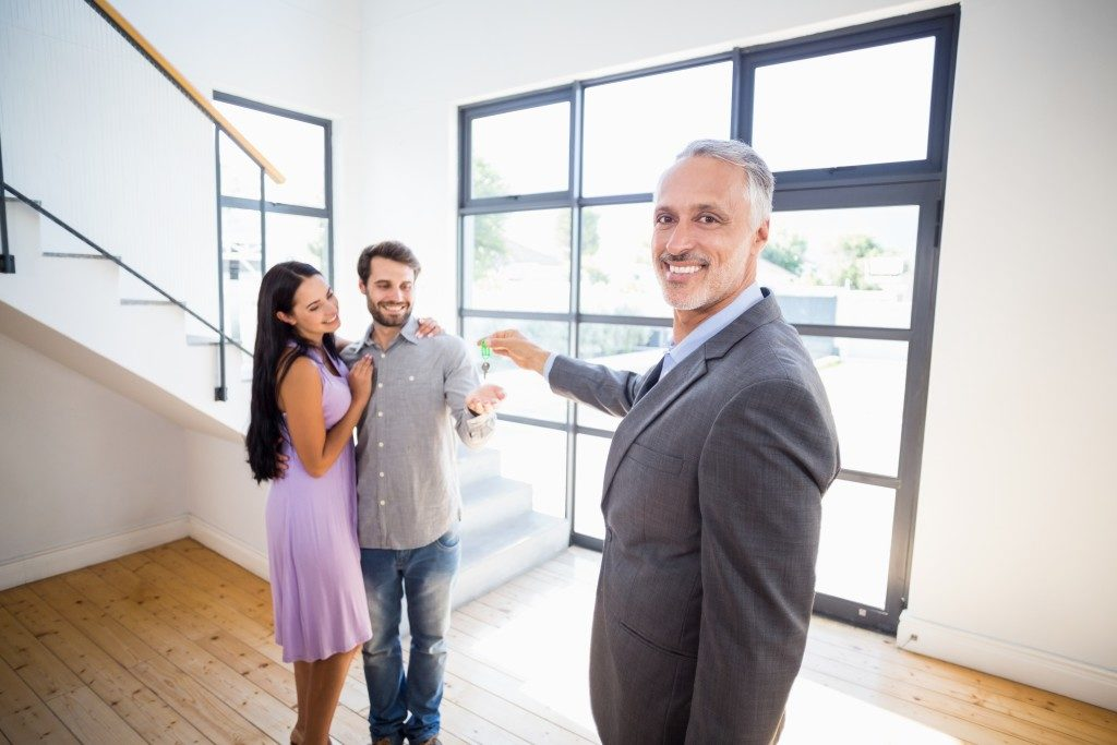 property owner handing over keys to tenants