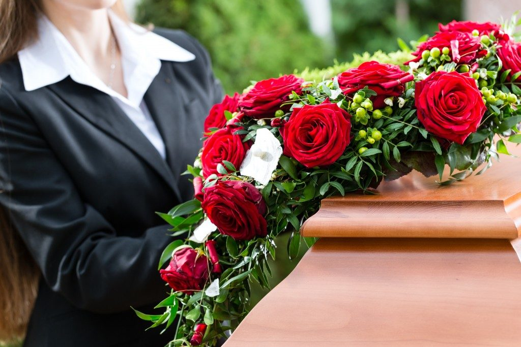Woman arranging the flowers on a casket