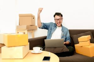 Happy entrepreneur sitting beside parcels