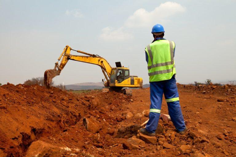 man in safety hat and uniform moniitoring an excavatior
