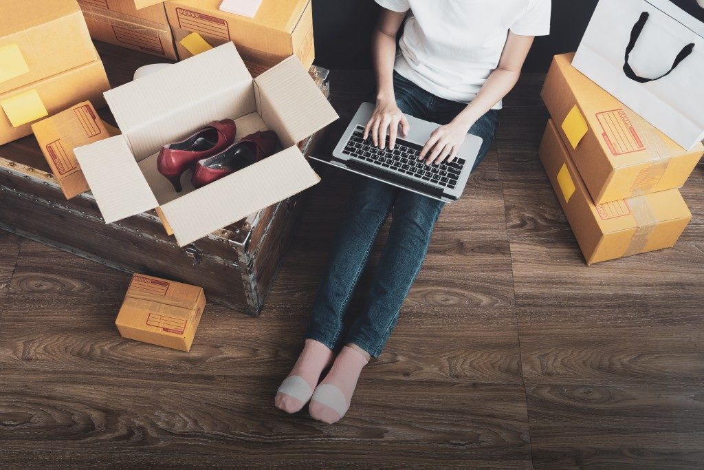 Woman surrounded by boxes shopping online