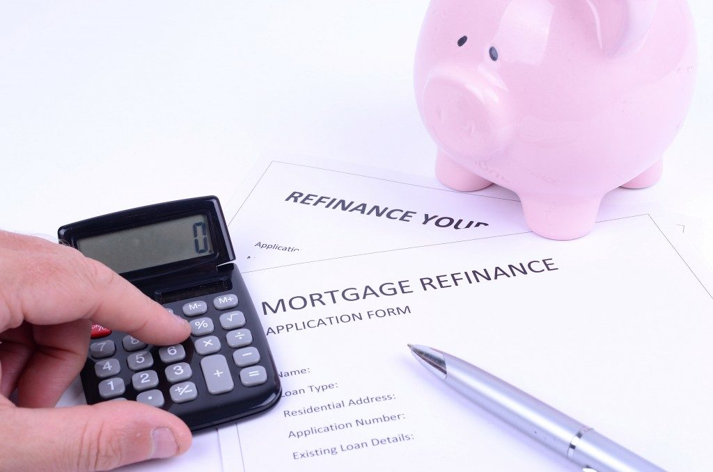 small calculator and piigy bank ont top of a mortgage refinance application form