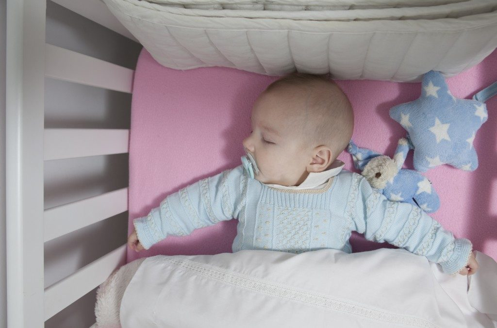 baby with pacifier sleeping in the crib