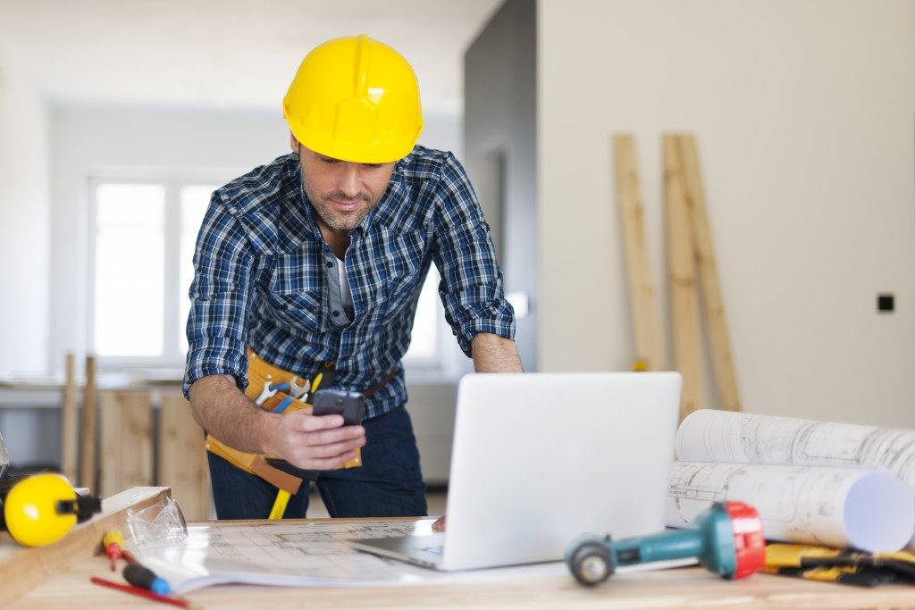 engineer or builder looking at his phone and computer