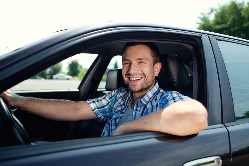 man smiling, driving his car