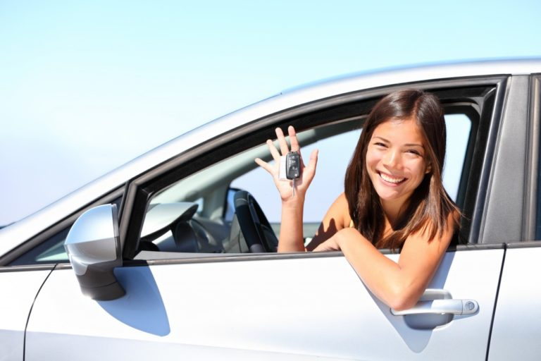 woman holding the keys to her new car