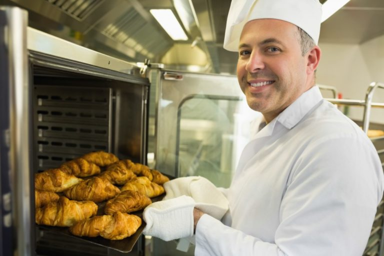 Baker bringing out croissants from the oven