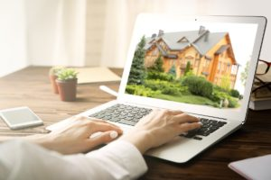 woman looking at a house on her laptop