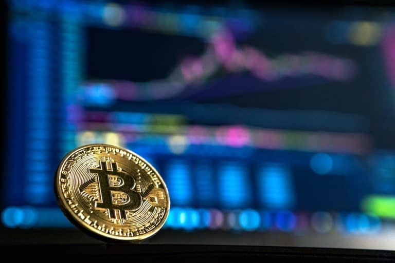bitcoin in front of a computer screen